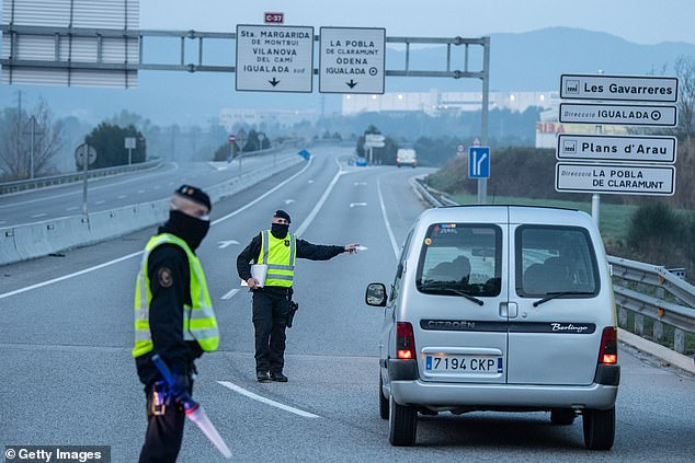 SPAIN: Catalan police officers stop a car trying to get into Igualada, one of the four towns closed down by regional authorities, at a checkpoint near Barcelona this morning