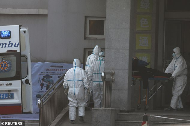 The picture taken on January 20 shows hazmat-donning medical staff transferring a coronavirus patient from an ambulance at the Jinyintan hospital in Wuhan to receive treatment