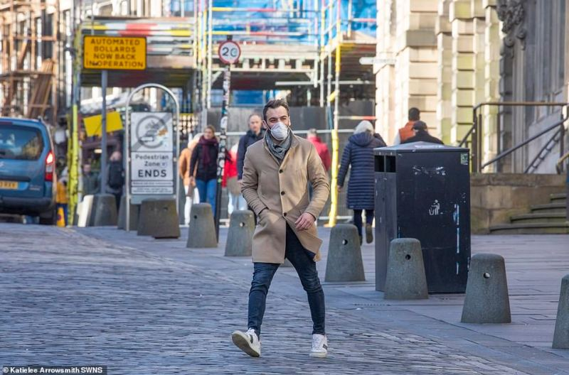 A man wearing a face mask is pictured on the usually-busy Royal Mile in Edinburgh as people stay away from public areas amid coronavirus worries