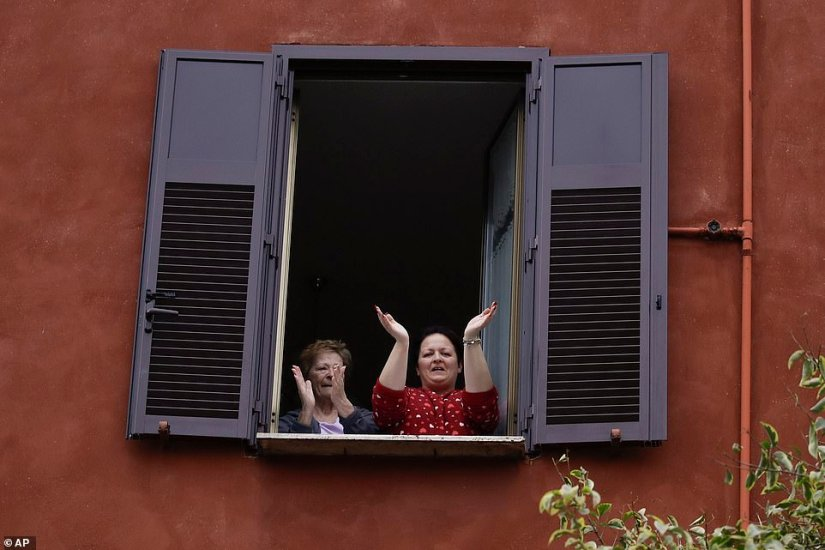 This morning two women applaud healthcare workers in Rome's Gabriella neighborhood