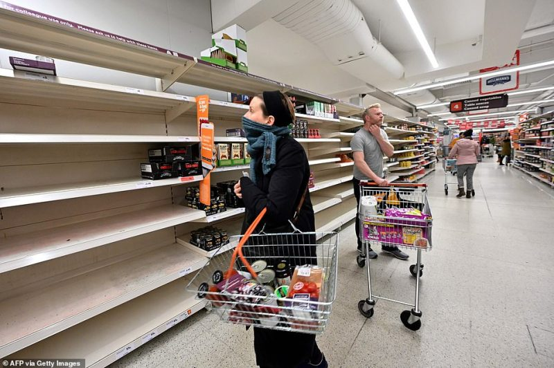 Shoppers are faced with partially empty shelves at a supermarket in London as consumers worry about product shortages as a result of the coronavirus