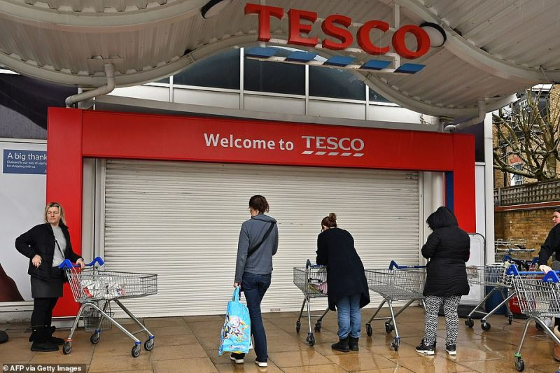 Shoppers wait in line for a supermarket to open its doors at Tesco in London on Saturday