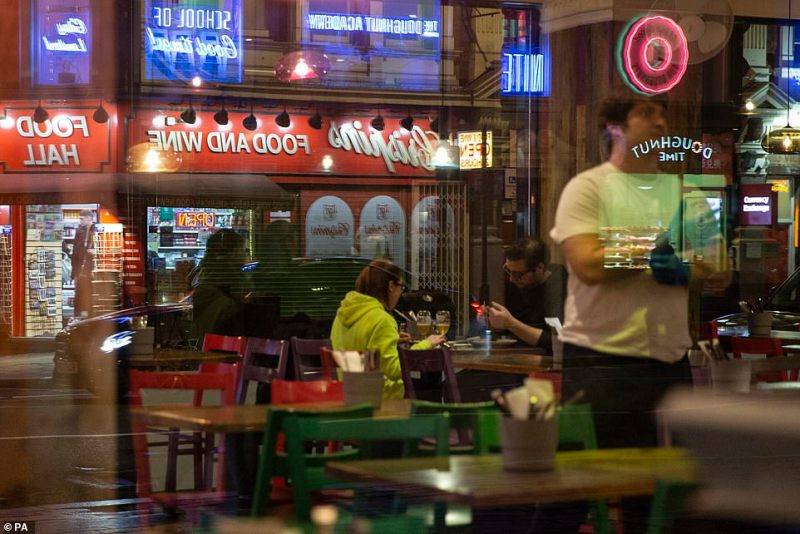 A couple dine alone in a restaurant in Soho as many choose to stay in following government warnings
