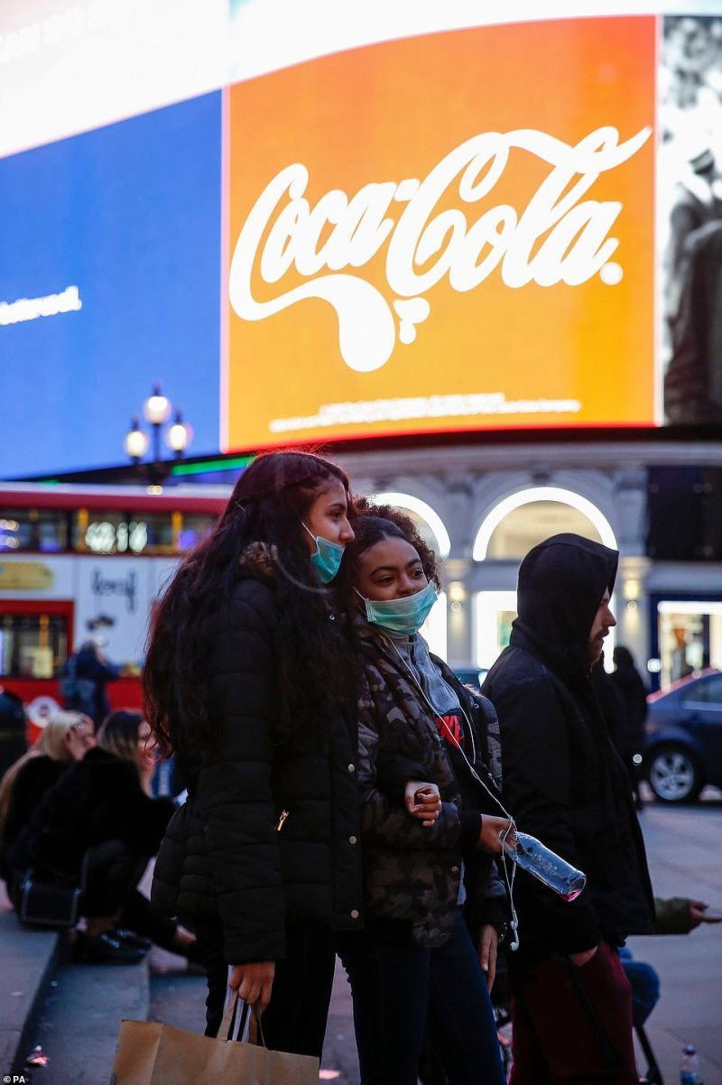Teenagers pose for a photo while wearing masks in Piccadilly Circus, London,on Saturday