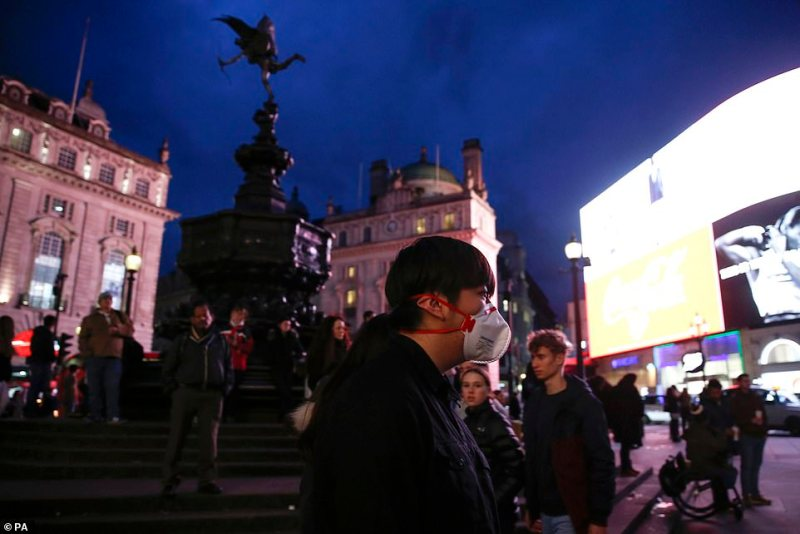 A man in a mask in Piccadilly Circus, London. Britain is yet to take the same measures as France and Italy and has not closed public venues