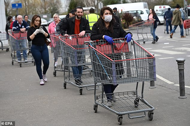 Shoppers queue to enter the Costco wholesale supermarket in north London as panic-buying grips the nation amid the outbreak