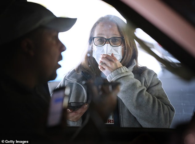 On Friday, President Donald Trump announced that Google was developing a website to help Americans determine whether and how to get tested. Pictured:Carroll Hospital Critical Care Unit Clinical Manager Stephanie Bakert talks to a person through his car window using a mobile phone before testing him for coronavirus in Maryland, March 16