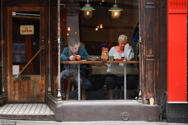 People look at their phones next to the window of a restaurant in Chinatown in London today
