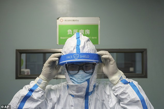 A doctor puts on an isolation outfit before entering the negative-pressure isolation ward in Jinyintan Hospital, designated for critical COVID-19 patients, in Wuhan in central China's Hubei province in February