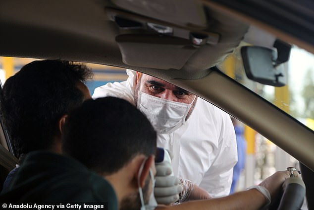 A health worker measures the body temperature of a passenger as a precaution against the coronavirus (COVID-19), in Qom, Iran yesterday, after the death toll in Iran from the novel coronavirus outbreak rose to 988
