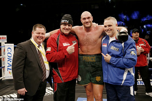 Fury poses with his team in 2015, before spending almost three years outside the ring