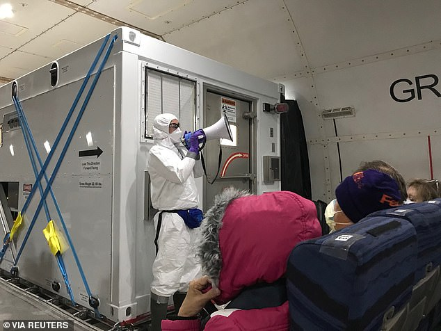 During the press briefing, the WHO also hit back at President Donald Trump for continuing to refer to the novel coronavirus as the 'Chinese virus.' Pictured:A US health official in front of a portable bio-containment unit speaks to US passengers evacuated from the Diamond Princess cruise ship to the US, February 17