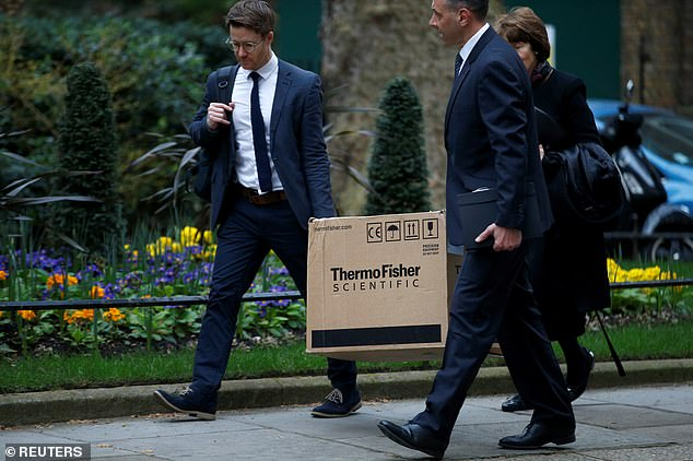 Two men wearing suits were pictured carrying a box from ThermoFisher – which makes coronavirus tests that give results in four hours – outside Downing Street this week