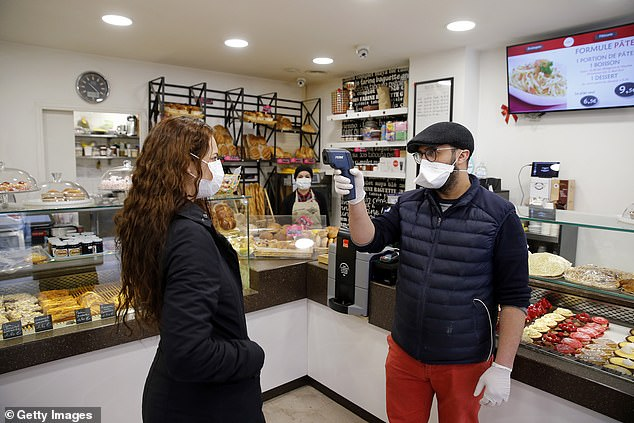 A baker wearing a mask and protective gloves scans the temperature of a customer wearing a protective mask using a front digital thermometer at the entrance to his bakery the day after the announcement by French President Emmanuel Macron of the French imprisonment of Wednesday noon to stem the spread of the coronavirus