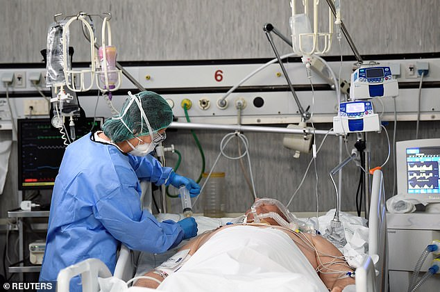Doctors and scientists around the world are scrambling to find a treatment or a vaccine for the coronavirus. Pictured, a medical worker treats a patient in intensive care in Cremona, Italy