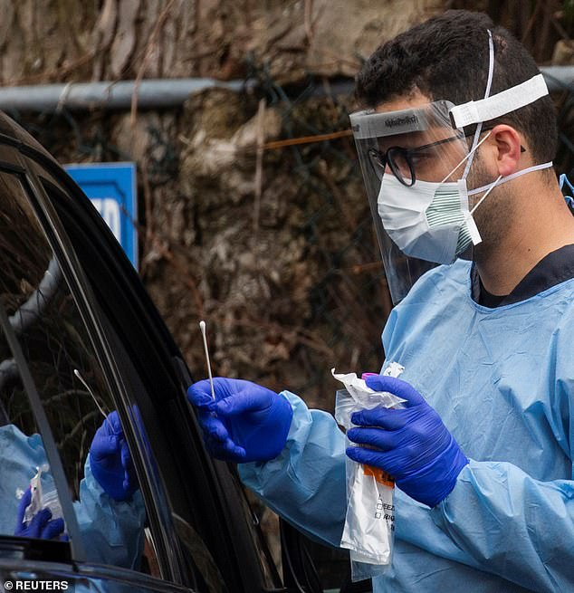 The UK has been criticised for potentially allowing tens of thousands of patients to go undiagnosed due to a lack of testing. Here, a medic tests a patient at a drive through screening centre in New Jersey