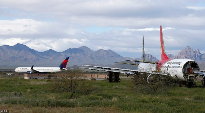 A recently landed Delta Air Lines plane is towed past two stripped passenger planes at Pinal Airpark