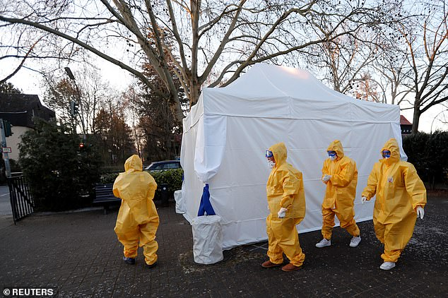 Doctors in yellow protective suits walk past a tent that is used as a coronavirus test center in Berlin's Reinickendorf district this morning