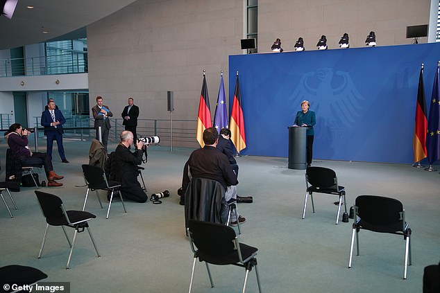 Journalists keep their distance from each other as they watch Angela Merkel hold a press conference on the coronavirus in Berlin yesterday