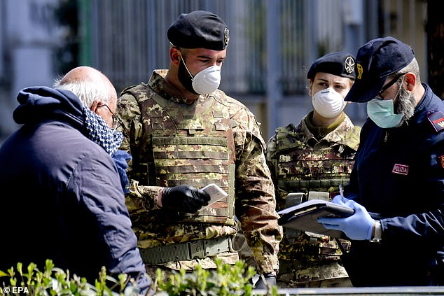 Italian Army soldiers and police jointly patrol the streets in Naples checking people's reasons for being out of their homes amid a coronavirus lockdown