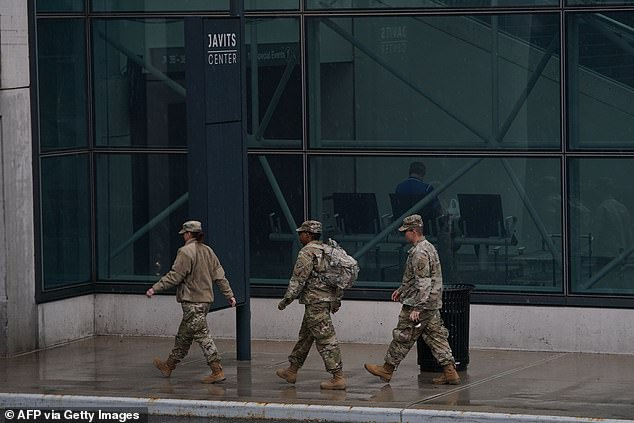 The National Guard is assisting New York and FEMA in setting up 1,000 additional beds in four 'hospitals' at the Javits Center in Midtown Manhattan. Pictured: Three National Guard members walk up to the Javits Center on Monday