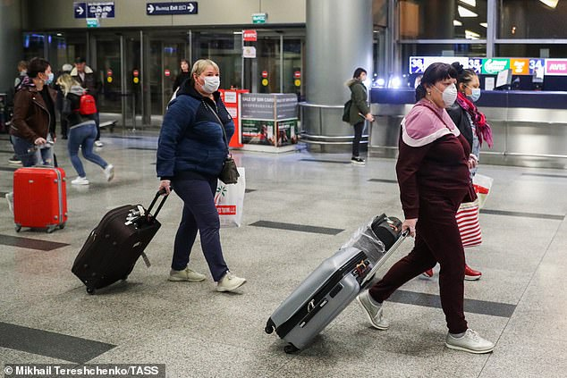Passengers wear face masks as they arrive atVnukovo International Airport in Moscow, Russia