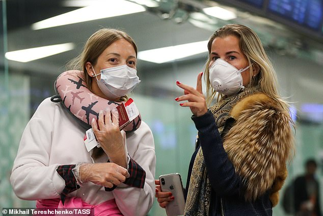 Two women wear face masks and plastic gloves as they wait for a flight atVnukovo International Airport today