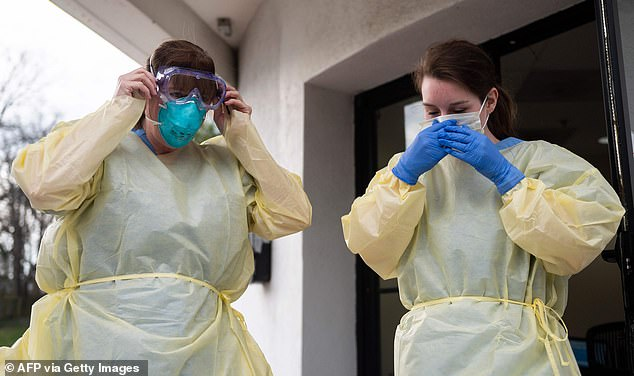 Health chiefs have confirmed there are problems with dwindling supplies globally. Pictured, health care workers put on their personal protective equipment before people arrive at a drive through testing site for coronavirus in Arlington, Virginia