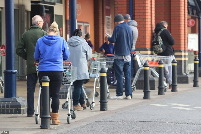 People queue today at a Sainsbury's supermarket at Colton, on the outskirts of Leeds, after the UK was put into lockdown