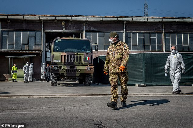 A masked Italian soldier stands in a street near an army truck in Ponte San Pietro, while soldiers are lined up to transport dead bodies in northern Italy