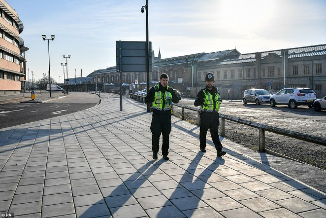 British Transport Police patrol the perimeter of Bristol Temple Meads train station, which is empty of rush-hour commuters and travelers