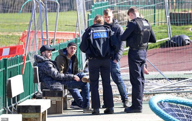 A group of young men are spoken to by Kent Police officers before being dispersed from a children's play area in Mote Park, Maidstone,