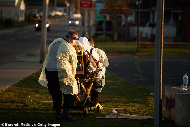 First responders from IU Health Bloomington hospital pick up a woman at the corner of 1st St and S. Walnut St who was sitting slumped over, and was saying she was having trouble breathing, and other COVID-19/Coronavirus symptoms in Bloomington, Ind.