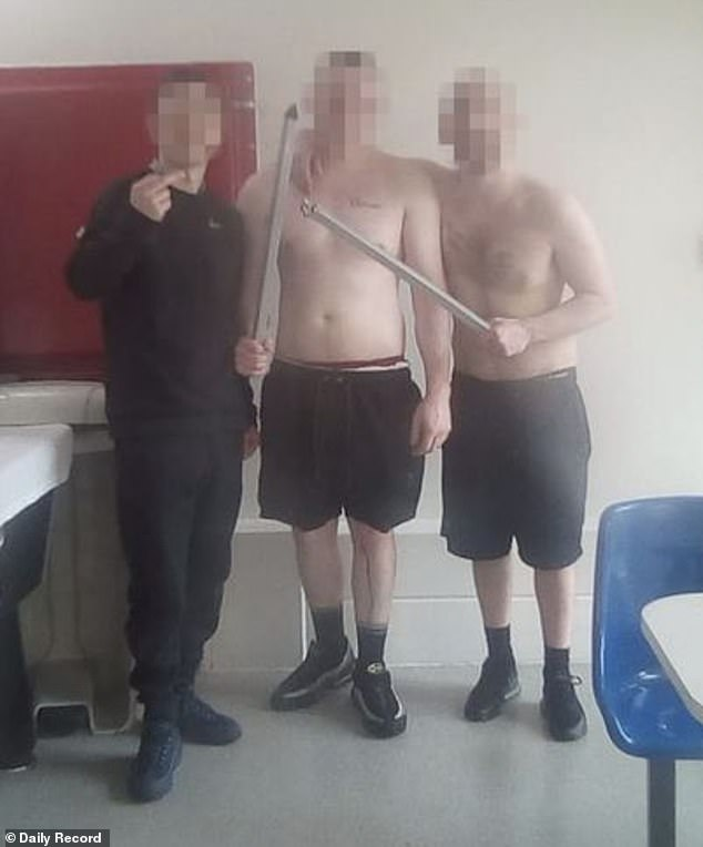Police were called to Addiewell Prison in West Lothian, Scotland, on Monday after rioting prisoners carrying metal bars were said to have 'smashed up' part of the jail (pictured, prisoners with lengths of metal)