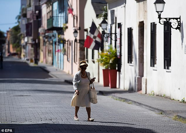 A woman walks near to the Nuestra Señora de la Altagracia church in Santo Domingo. The church has been closed due restrictions imposed by the Domincan Republic government which ban large public gatherings