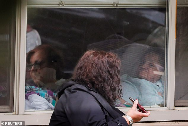 Earnest said that if she told one physician that somebody had red eyes, a hospital bed would be made ready for them. Pictured:Sisters Carmen Gray (reflected at left) and Bridget Parkhill visit their mother Susan Hailey, who is recovering from coronavirus at Life Care, March 24