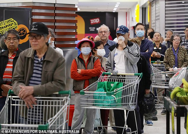 Shoppers are urged to keep a trolley's length away from each other. Pictured are shoppers waiting for Woolworths to open in western Sydney last week
