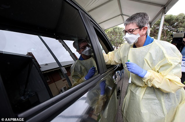 A nurse takes a sample from a driver at a new COVID-19 drive-through testing facility at Hampstead Rehabilitation Centre in Adelaide