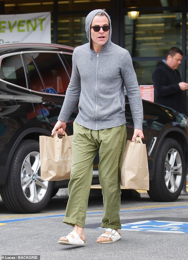 Casual: Pine covered up in a light grey hoodie and olive green pants, while slipping his feet into white sandals