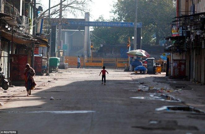 A boy plays on a near-empty street during a lockdown amid a coronavirus disease (COVID-19) outbreak in New Delhi