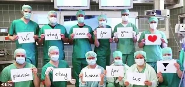 Australian doctors have joined the global effort to call for people to stay at home. Pictured: Doctors holding up signs reading 'we stay here for you, please stay home for us'