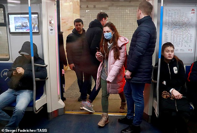 Shoes should be left outside or directly inside the front door to avoid trekking germs and bacteria collected on trains or buses through the house (pictured, a woman wearing a face mask boards a train in Moscow Underground on March 11, 2020)