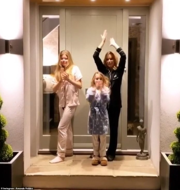 Paying tribute: Meanwhile Amanda Holden took to her doorstep with daughters Lexi, 14, and Hollie, eight, for the round of applause in honour of NHS workers