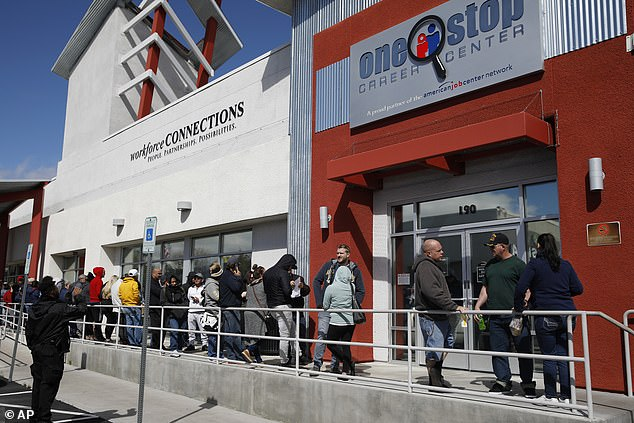 US unemployment claims have surged to 3.28million - four times the previous record - as a result of the pandemic's crippling impact on the economy. People are shown waiting in line at the unemployment office in Las Vegas