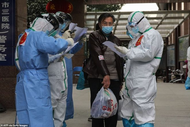 Medical staff check information as patients infected by the COVID-19 coronavirus are transferred from Wuhan No.3 Hospital to Huoshenshan Hospital in China's central Hubei province on March 4, 2020