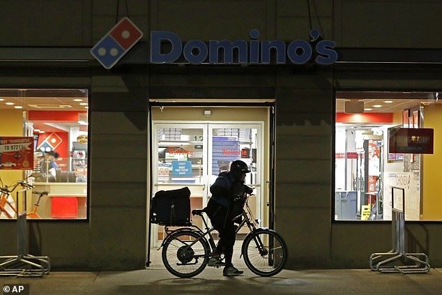 A delivery driver leaves a Domino's Pizza restaurant in downtown Seattle on a bike after all restaurants were ordered closed