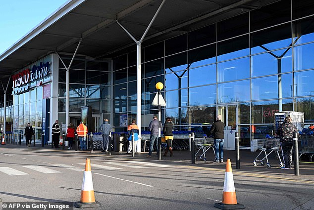 The UK's coronavirus social distancing limit is at least four times too short, a study has warned. Pictured: People keep their distance from each other as they queue to get into Tesco in Stoke-on-Trent on Saturday