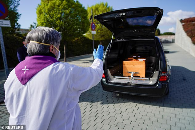 The army now being handed emergency powers to transfer bodies because undertakers can't cope. Pictured: Priest gives a response in front the coffin of a woman who died of coronavirus disease