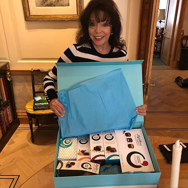 SWEET SECLUSION: Joan Collins, 86, unwraps a bumper supply of chocolate
