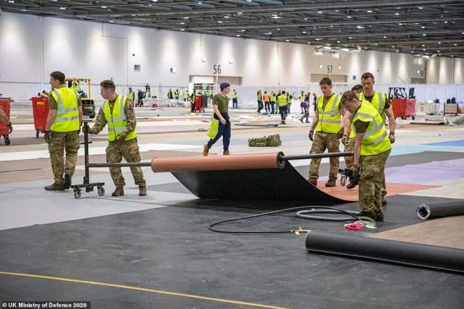 Soldiers roll out mats and assist in the final preparations for the new field hospital in London as the country continues to control the coronavirus outbreak